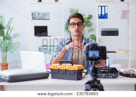 Vlogger recording computer repair on camera for vlog blog