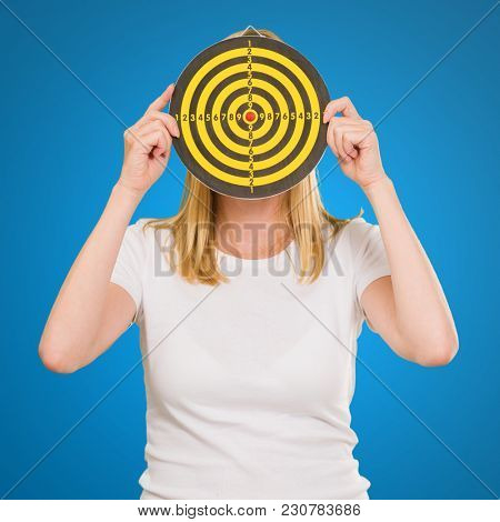 Portrait  Of A Woman Holding Dartboard On Blue Background