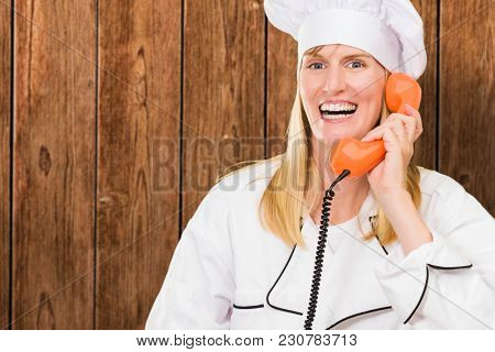 Female Chef Holding Telephone against a wooden background