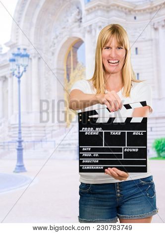 Happy Woman Holding Clapper Board, outdoor