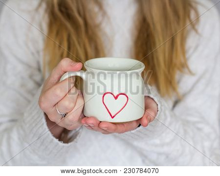 A Mid Section Of A Young, Blonde Haired Girl Wearing A Cosy Sweater And Holding A Hot Cup Of Coffee