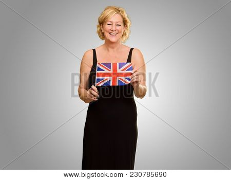 Happy Mature Woman Holding British Flag Isolated On Grey Background