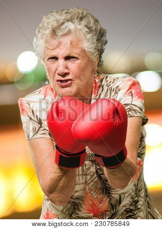 Angry Mature Woman Wearing Boxing Gloves, Outdoors