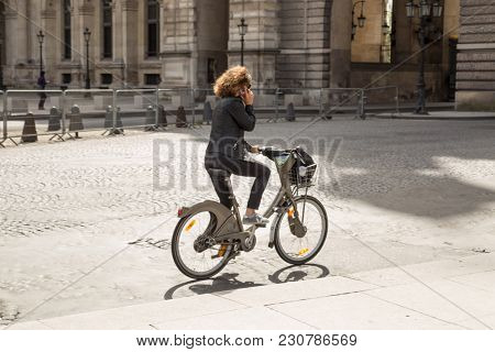 Paris, France - March 28, 2017: Woman rides in Paris on self-service bike rental
