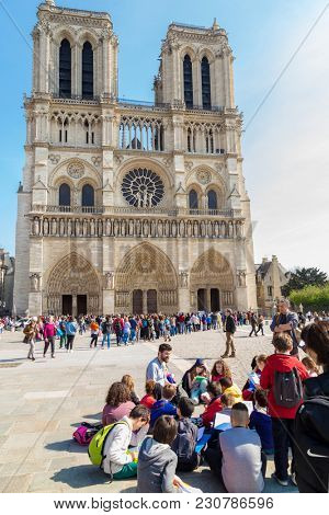 Paris, France, March 27 2017: A group of children with colourful backpacks on a trip to famous Notre Dame cathedral facade saint statues.