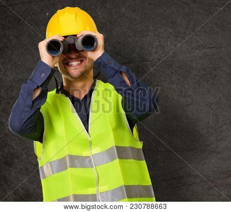 Young Engineer Looking Through Binoculars, Indoors