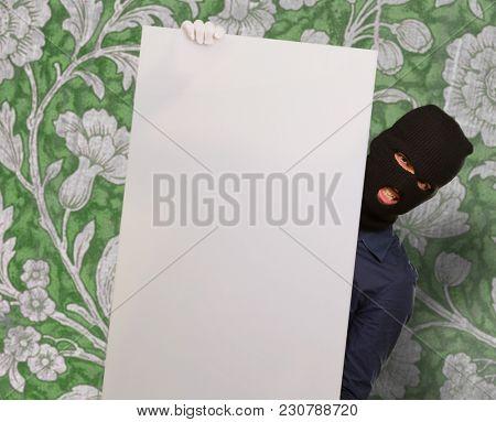 Burglar Man Holding Blank Placard Against Wallpaper