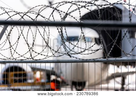 Airport Security Zone. Blurred Aircraft Behind A Barbed Wire Fence. Illustration Of The Incident In