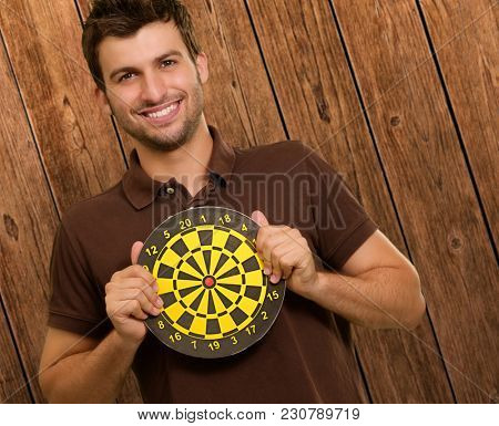 Portrait Of A Man Holding A Dartboard On Wooden Background