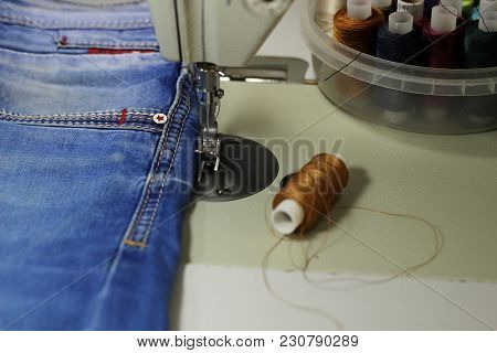 On The Table Of The Sewing Machine Lie Denim Fabrics, Close-up, Next To The Thread And Scissors.