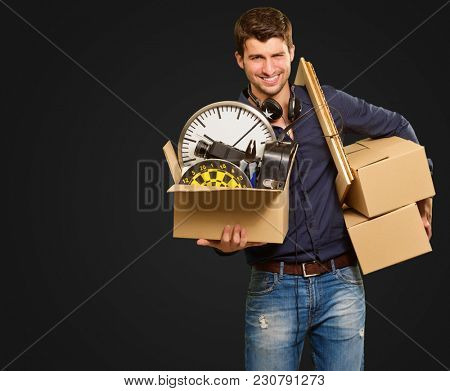 Young Man Holding Cardboxes Gesturing On Black Background