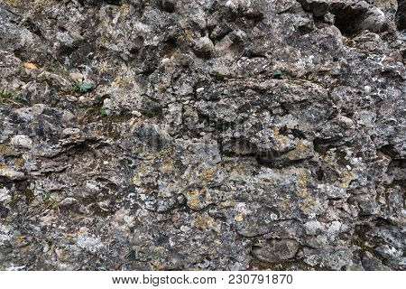 Texture Of Old Mossy Weathered Rocks With Cracks.