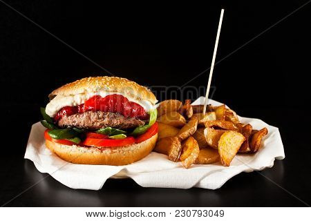 Fresh Tasty Burger And French Fries On Wooden Table.  Potato Wedges