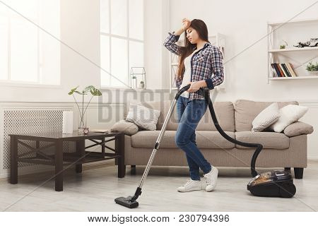 Young Woman Tired Of Spring Cleaning House, Washing Floor With Vacuum Cleaner, Copy Space