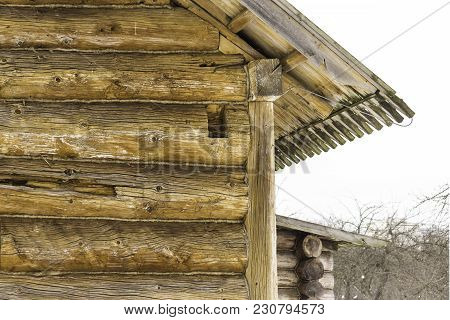 Wooden Restored Barn. Built In The 18th Century. A Log Wall And A Corner Joint Of Logs. Interesting