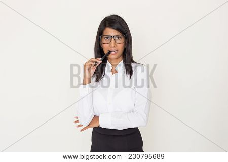 Pensive Indian Woman In Formalwear And Glasses Holding Pen Near Teeth. Young Sexy Business Lady Flir