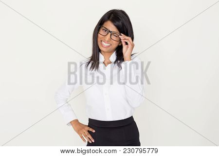 Portrait Of Happy Indian Woman In Formalwear Touching Glasses And Winking At Camera. Young Secretary