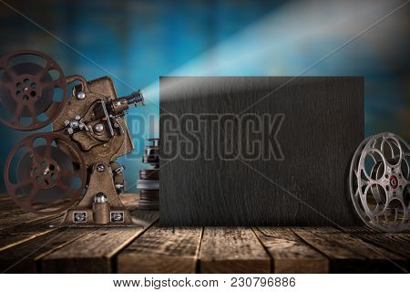 Cinema concept of vintage film reels, black board and projector ond old wooden background.