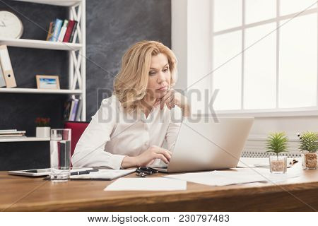 Serious Businesswoman Working On Laptop At Office. Businesswoman Typing Something On Computer While