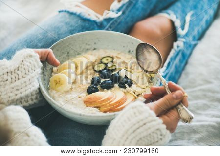 Healthy Winter Breakfast In Bed. Woman In Woolen Sweater And Shabby Jeans Eating Vegan Almond Milk O