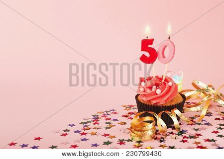 50th Birthday Cupcake With Candles, Sprinkles And Ribbon On Pink Background. Card Mockup, Copy Space