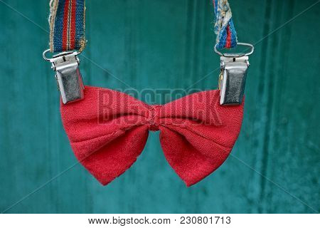 Red Old Bow Tie On Suspenders On A Green Background