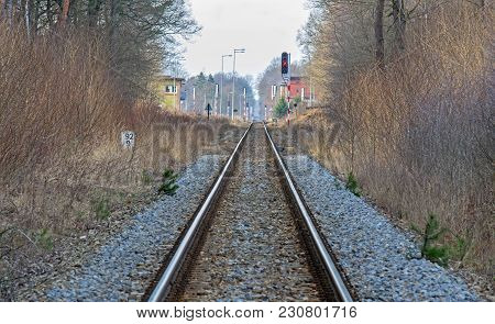 A Straight Section Of Railway Tracks Leading To A Small Railway Station. The Embankment Is Covered W