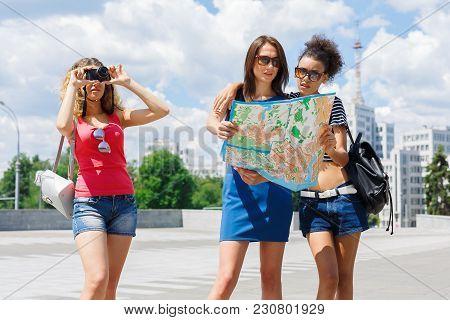 Three Girls With Paper Map Outdoors. Female Friends Walking Around Summer City, Taking Photos And Ha