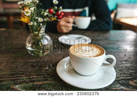 Two Cups Of Coffee And A Vase Of Flowers On A Wooden Table, The Man Holds In Her Hand One Cup Of Cof