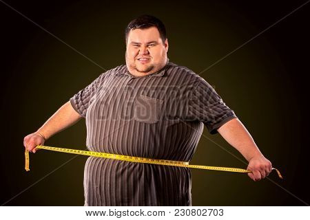 Man belly fat with tape measure weight loss around body on black background. Person is happy that he defeated anorexia.