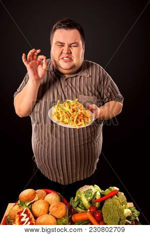 Diet failure of fat man eating fast food. Overweight person who spoiled healthy food by eating french fries. Junk meal leads to obesity. Man struggles with hunger for all his strength.