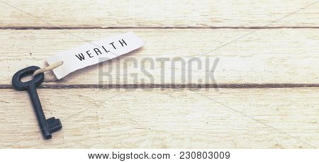 Key And Keyring With The Word Wealth Over White Wooden Table. Toned