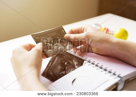 Woman Placing Baby's Sonogram Into Baby's First Year Memory Book