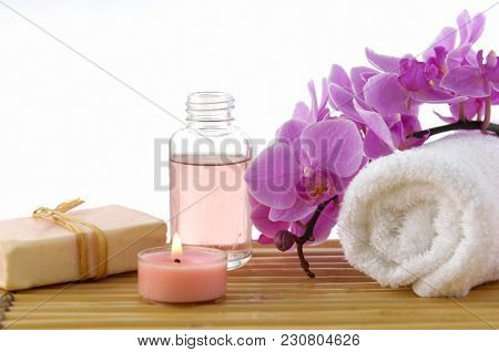 Set of orchid with massage oil, soap, candle, towel, on mat