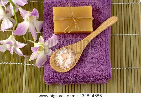 Set of orchid with salt in spoon, towel, soap on mat
