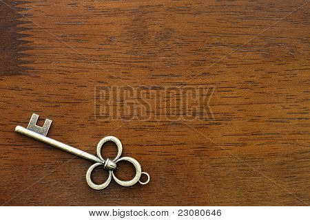 close up of old key on a wooden table poster