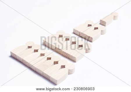 Wooden Figures Of People On A White Background In The Form Of A Pyramid Of Social Hierarchy. The Con