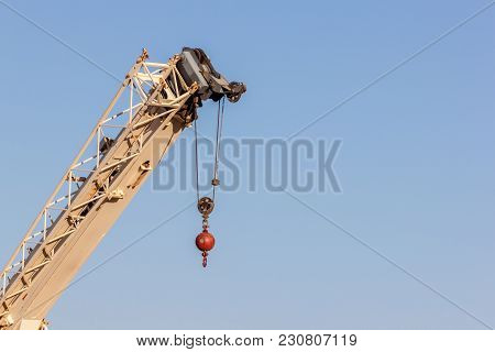 Construction Crane Hook Lifting Machinery Over Natural Clear Blue Sky With Lots Of Copy Space For Yo