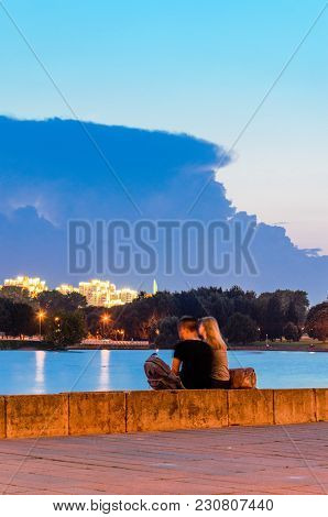 Minsk, Belarus - August 16, 2017: Young Couple Watching A Sunset In Front Of Cityscape Sitting On A