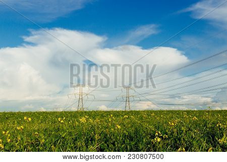 High Voltage Power Lines And Transmission Towers In Agricultural Fields In Normandy, France On Coudy