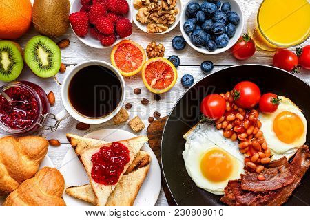 Breakfast Including Coffee, Fried Egg, Bacon, Beans, Toast, Croissant, Orange Juice, Fruits And Berr