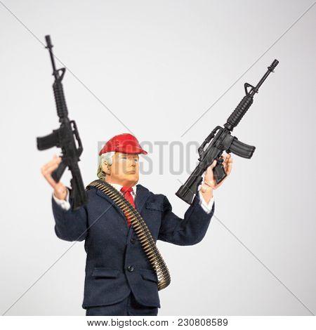 MARCH 11 2018: Caricature of US President Donald Trump brandishing AR 15 semi-automatic assault rifles - Second Amendment / NRA concept