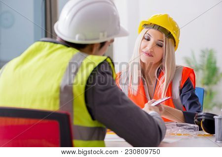 Construction workers having discussion in office before starting
