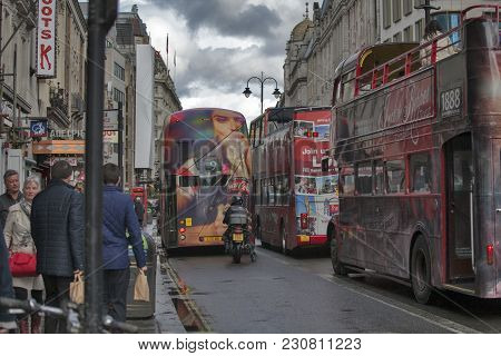 London, England - March 12, 2017 Double Decker Buses With Advertising On The Sides Against The Backg
