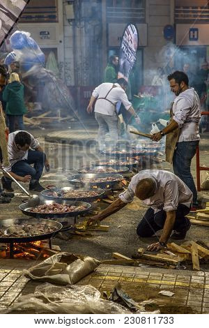 Valencia, Spain - 3/12/2018: Crew Of Many Cooks Preparing Many Pans Of Paella On The Street For The