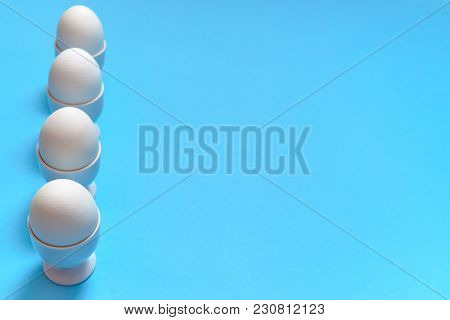 White Eggs Standing On Egg Cup Isolated On Blue Background, Copy Space. Row Of Boiled Eggs In Stand.