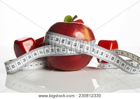 Red Apple With Measuring Tape And Red Weight Dumbbells For Diet Concept On White Background, Close-u