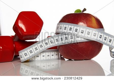 Fitness Composition With Red Dumbbells And Red Apple With Measuring Tape On White Background, Close-