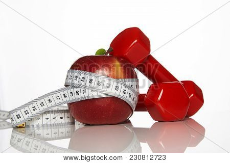 Fresh Appetizing Red Apple And Red Colored Dumbbells Tied With A Measuring Tape On White Background,