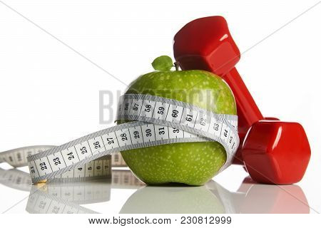 Red Dumbbells, Fresh Green Apple And White Measuring Tape On A White Background, Close-up. Healthy L